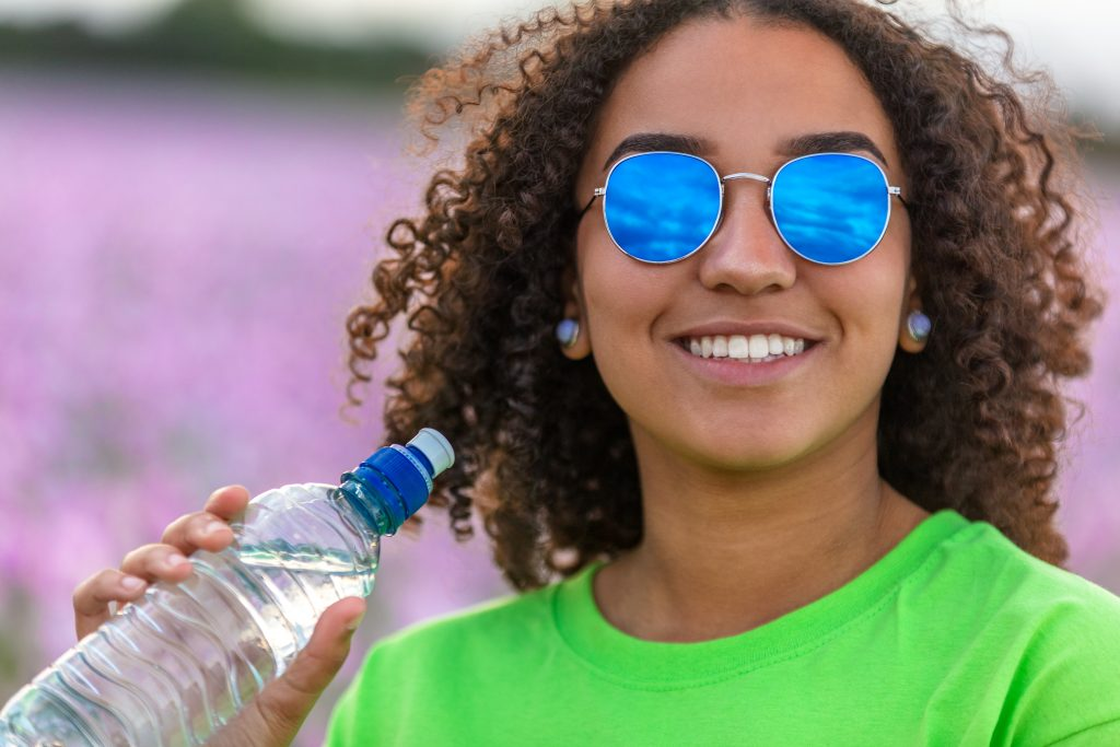 Girl Wearing Sunglasses Outside Drinking Water